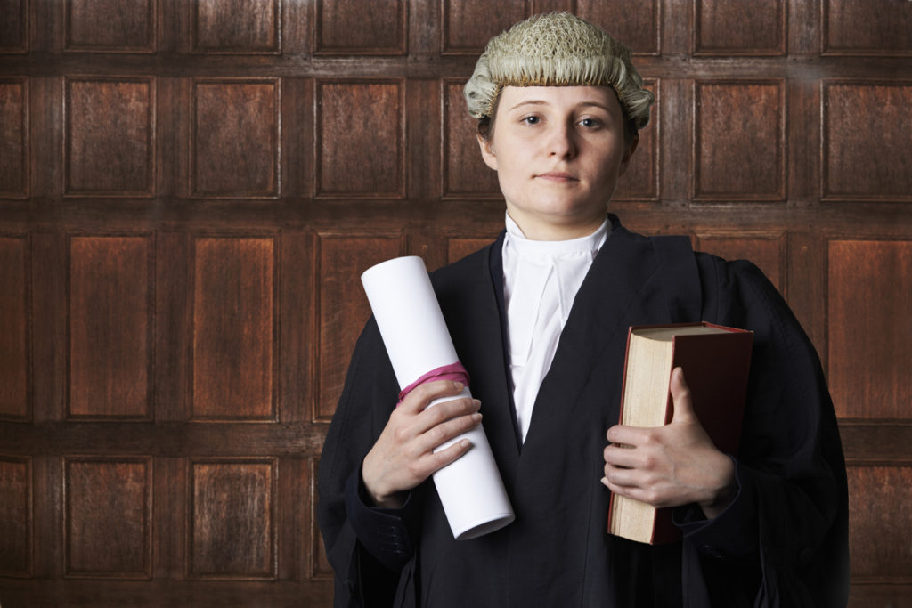Portrait Of Female QC Lawyer In Court Holding Brief And Book